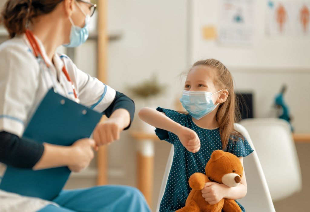 Pediatra saludando a niña con el codo