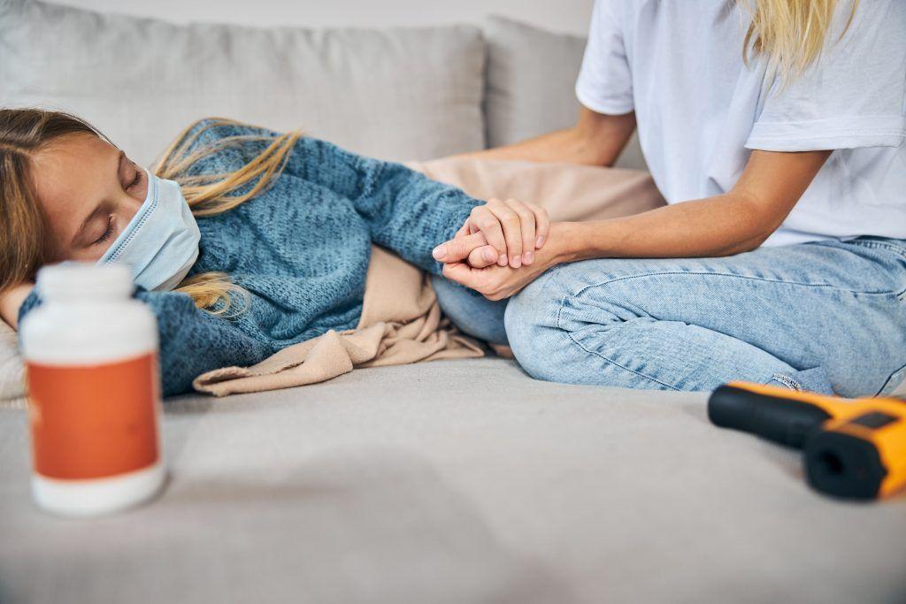 Mujer recostada en la cama, padeciendo el síndrome poscovid-19